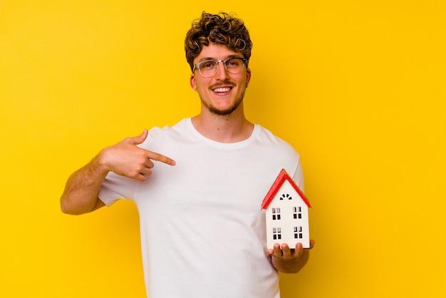 シャツのコピースペースを手で指している黄色の壁の人に隔離されたモデル家を保持している若い白人男性、誇りと自信を持って