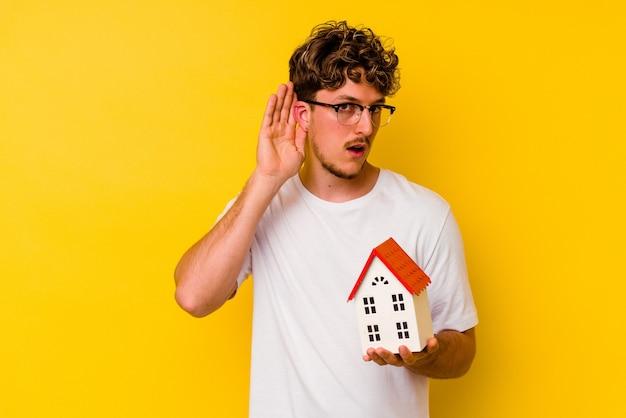 ゴシップを聴こうとしている黄色の壁に隔離されたモデル家を保持している若い白人男性。