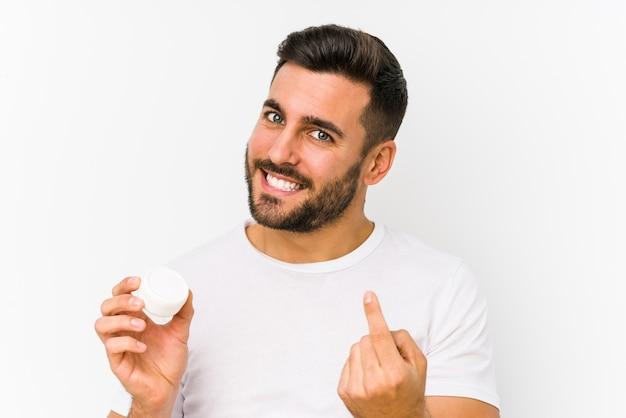Молодой кавказский мужчина держит увлажняющий крем, указывая пальцем на вас, как будто приглашая подойти ближе.
