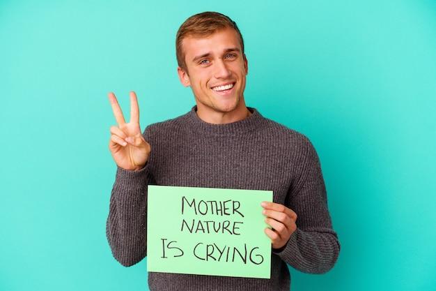 母なる自然を持った若い白人男性は、勝利のサインを示し、広く笑う青い背景に分離されたプラカードを泣いています。