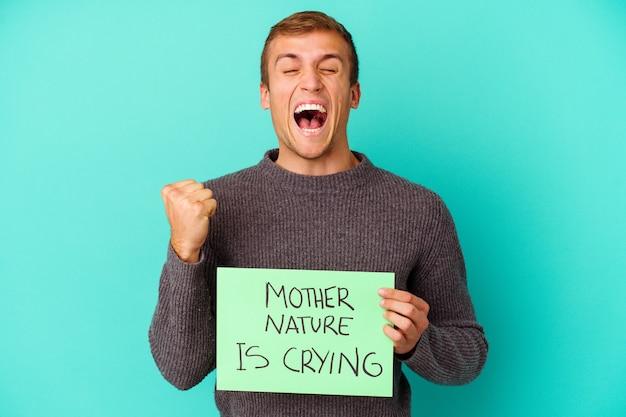 Молодой кавказский человек, держащий мать-природу, плачет с плакатом, изолированным на синем, беззаботно и возбужденно аплодирует. концепция победы.