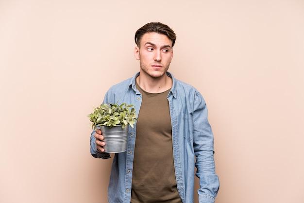 植物を持っている若い白人男性は混乱し、疑わしくて不安を感じます。