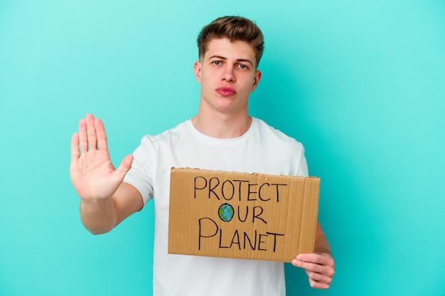 青い背景に分離された私たちの惑星のプラカードを保護する保持している若い白人男性