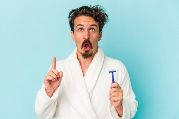 열린 입으로 거꾸로 가리키는 파란색 배경에 고립 된 면도날을 들고 젊은 백인 남자.