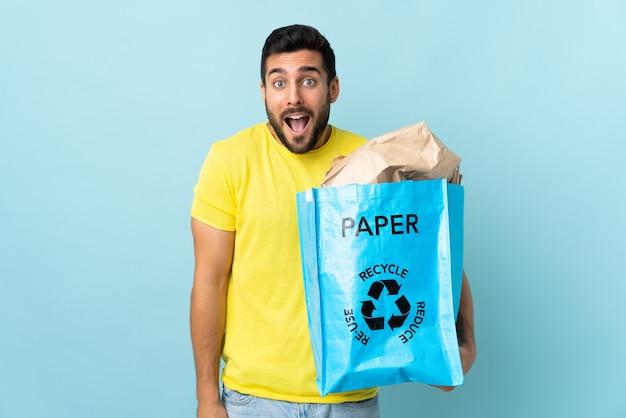 驚きとショックを受けた表情で青に分離されたリサイクルバッグを保持している若い白人男性