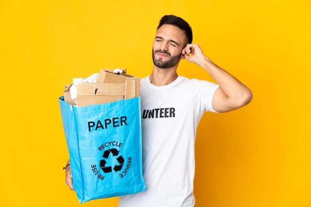 欲求不満と耳を覆う白い背景で隔離のリサイクルする紙でいっぱいのリサイクルバッグを保持している若い白人男性