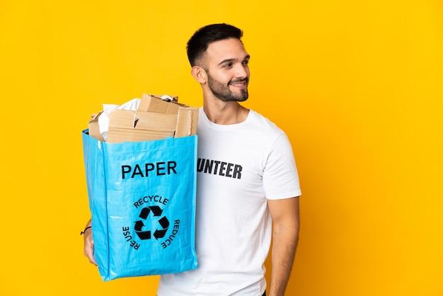 Молодой кавказский мужчина держит мешок для рециркуляции, полный бумаги для переработки, изолирован на белом фоне, смотрит в сторону и улыбается