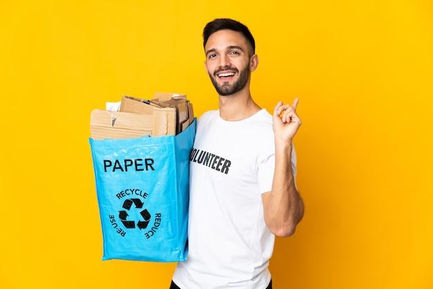 Молодой кавказский мужчина держит мешок для рециркуляции, полный бумаги для переработки, изолирован на белом фоне, указывая назад