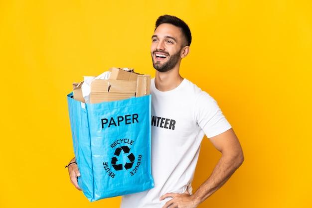 Молодой кавказский мужчина держит мешок для рециркуляции, полный бумаги для переработки, изолирован на белом фоне, позирует с руками на бедрах и улыбается