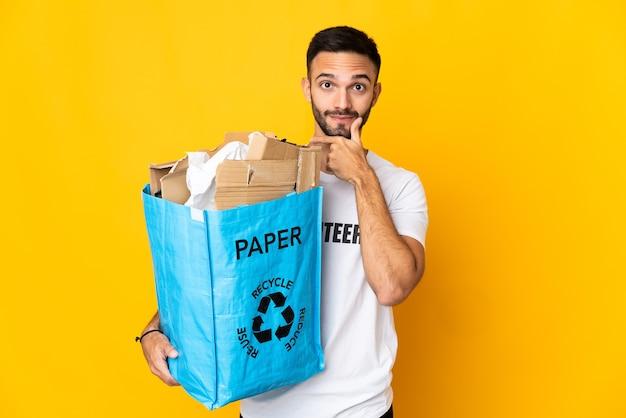 Молодой кавказский мужчина держит мешок для рециркуляции, полный бумаги для переработки, изолирован на белом фоне