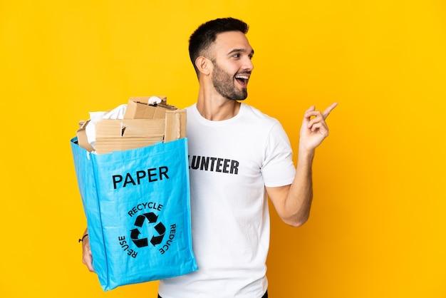 Молодой кавказский мужчина держит мешок для переработки, полный бумаги для переработки, изолирован на белой стене, намереваясь реализовать решение, подняв палец вверх