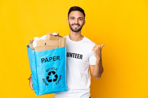製品を提示する側を指している白い壁に隔離されたリサイクルする紙でいっぱいのリサイクルバッグを持っている若い白人男性