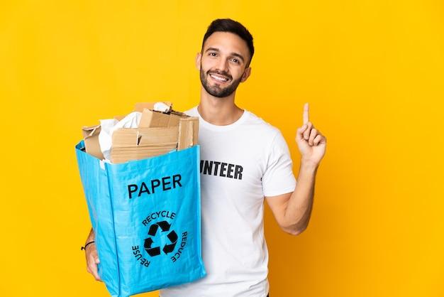 最高の兆候を示し、指を持ち上げて白い壁に隔離されたリサイクルする紙でいっぱいのリサイクルバッグを保持している若い白人男性