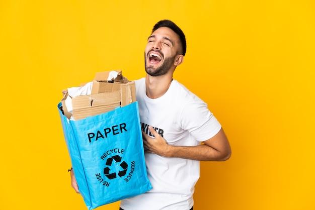 Молодой кавказский мужчина держит мешок для рециркуляции, полный бумаги для переработки, изолирован на белой стене, много улыбаясь