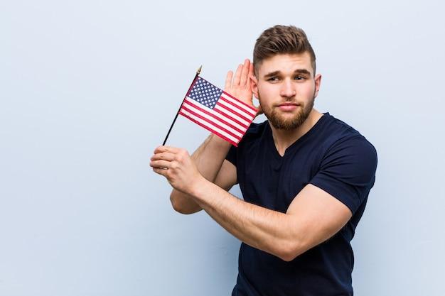 Молодой кавказский человек держа флаг соединенных штатов пробуя слушать сплетню.