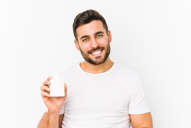 ビタミンボトルを持っている若い白人男性は、幸せ、笑顔、陽気な孤立しました。