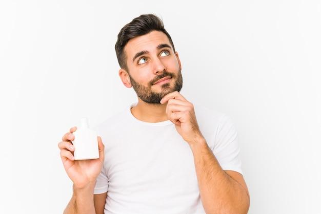 疑わしいと懐疑的な表現で横向きに孤立したビタミンボトルを保持している若い白人男性。