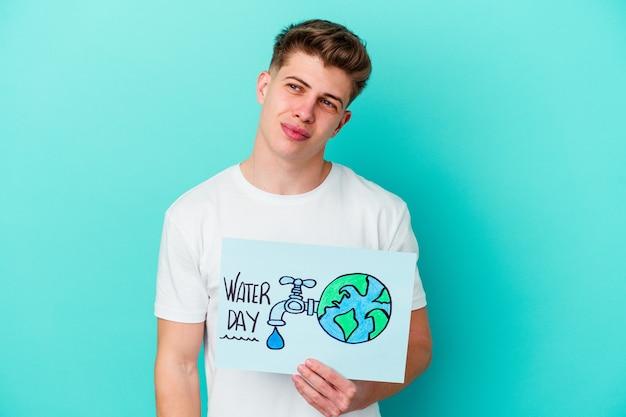 青で隔離の水の日のプラカードを保持している若い白人男性