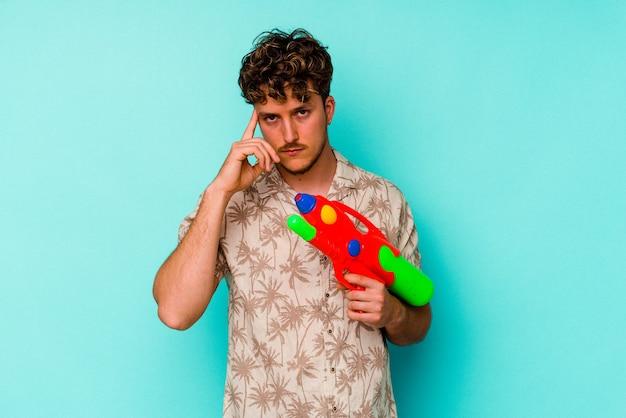 Молодой кавказский человек, держащий водяной пистолет, изолированный на синем фоне, указывая висок пальцем, думая, сосредоточился на задаче.