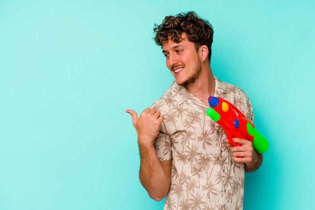 Молодой кавказский человек, держащий водяной пистолет, изолированный на синем фоне, показывает пальцем, смеясь и беззаботно.