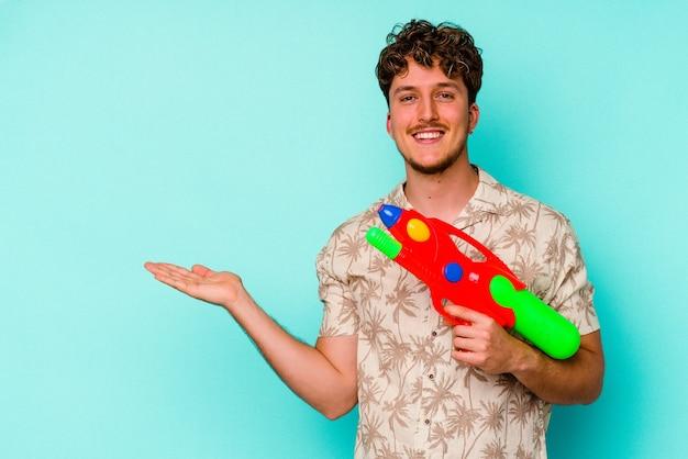 손바닥에 복사 공간을 표시 하 고 허리에 다른 손을 잡고 파란색 배경에 고립 된 물 총을 들고 젊은 백인 남자.