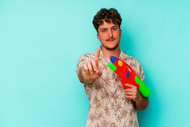 Молодой кавказский человек, держащий водяной пистолет, изолированный на синем фоне, показывает номер один пальцем.