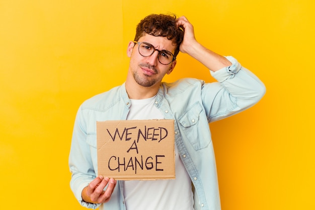 Молодой кавказский мужчина держит плакат с надписью «нам нужны перемены» в шоке, она вспомнила важную встречу.