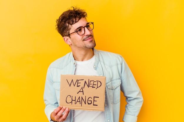 私たちを保持している若い白人男性は、目標と目的を達成することを夢見て孤立した変更プラカードが必要です