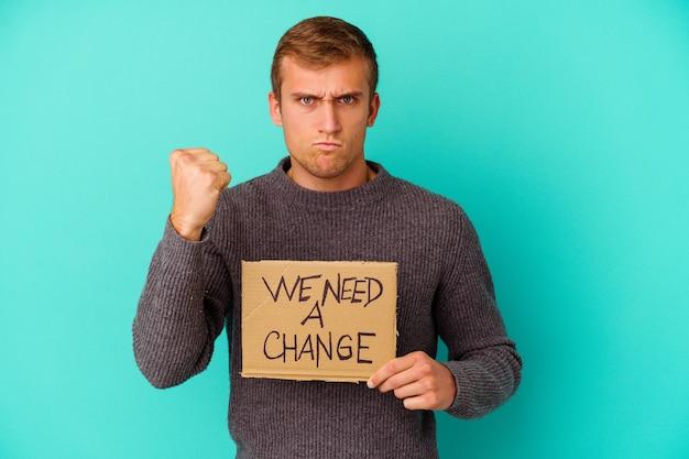 Молодой человек кавказской, держащий, нам нужен плакат изменения, изолированный на синем фоне, показывая кулак к камере, агрессивное выражение лица.