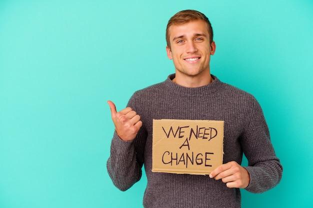 Молодой кавказский мужчина держит плакат с надписью «нам нужно изменение» на синем фоне, улыбаясь и поднимая палец вверх