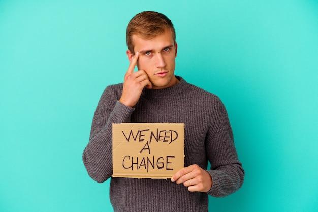 私たちを保持している若い白人男性は、タスクに焦点を当て、考え、指で彼の寺院を指している青い壁に分離された変更プラカードが必要です。
