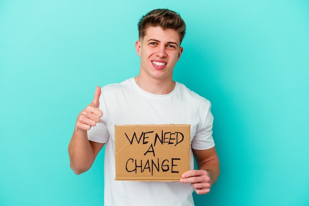 Молодой кавказский мужчина держит табличку с надписью «нам нужно изменение», изолированной на синей стене