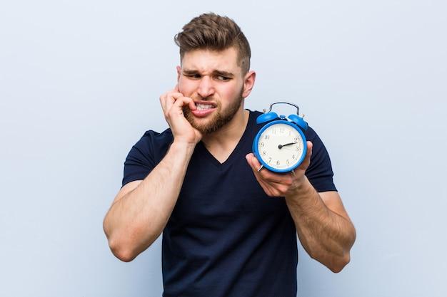 目覚まし時計を持っている若い白人男性が爪を噛んで、神経質で非常に心配しています。