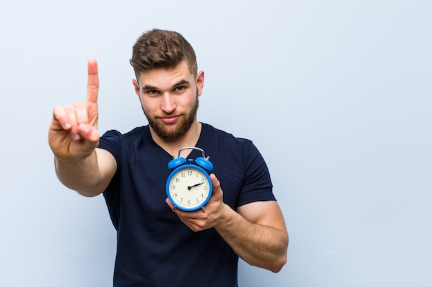Young caucasian man holding alarm clock showing number one with finger.