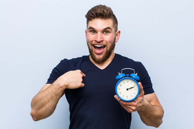 Young caucasian man holding alarm clock surprised pointing at himself, smiling broadly.