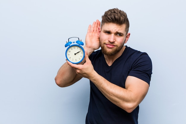 Young caucasian man holding alarm clock trying to listening a gossip.
