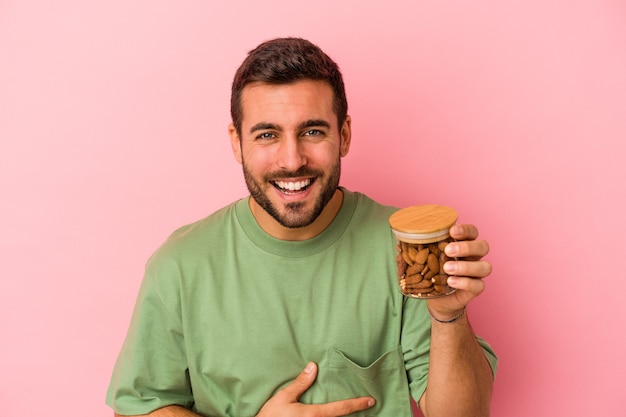 Young caucasian man holding an almond jar isolated on pink background laughing and having fun.