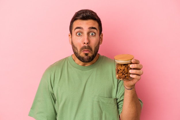 Young caucasian man holding an almond jar isolated on pink background shrugs shoulders and open eyes confused.
