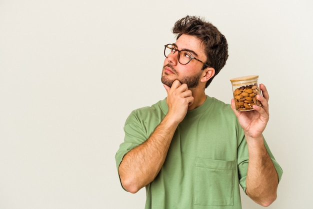Young caucasian man holding an almond jar isolated on white background looking sideways with doubtful and skeptical expression.
