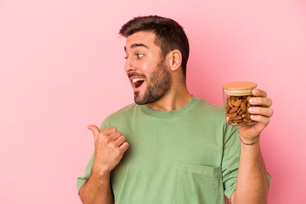 ピンクの背景に隔離されたアーモンドの瓶を持ち、親指を離して、笑いながら屈託のない若い白人男性。