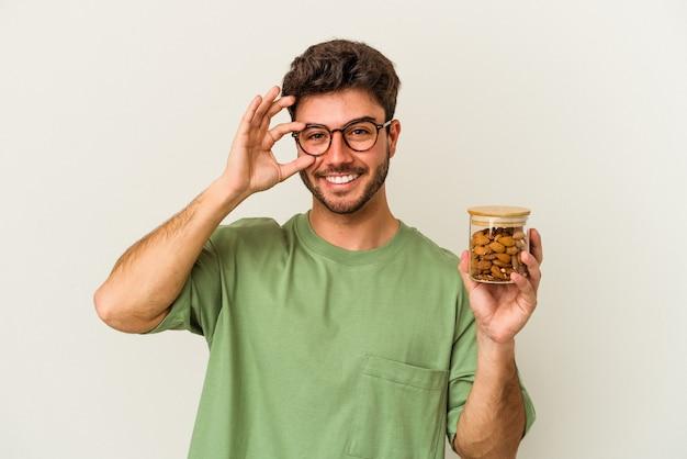 白い背景に隔離されたアーモンドの瓶を持った若い白人男性は、目には ok のジェスチャーを維持して興奮しています。
