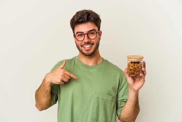 白い背景にアーモンドの瓶を保持している若い白人男性が、シャツのコピー スペースを手で指し、誇りと自信を持って