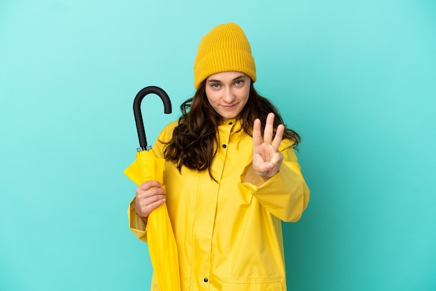 幸せな青い背景に分離された傘を持って、指で3を数える若い白人男性