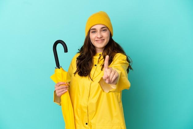 파란색 배경에 격리된 우산을 들고 손가락을 들고 들어올리는 백인 청년