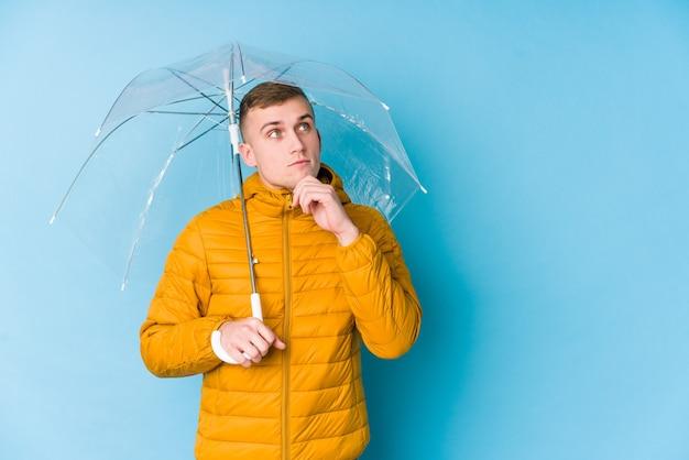 疑わしいと懐疑的な表情で横向きの傘を持っている若い白人男性。