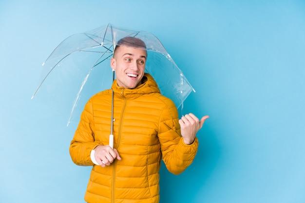 Молодой человек кавказской, проведение зонтик указывает пальцем в сторону, смеется и беззаботный.