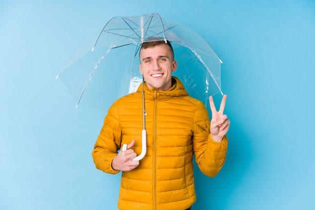 Молодой кавказский человек держа номер два показа зонтика с пальцами.
