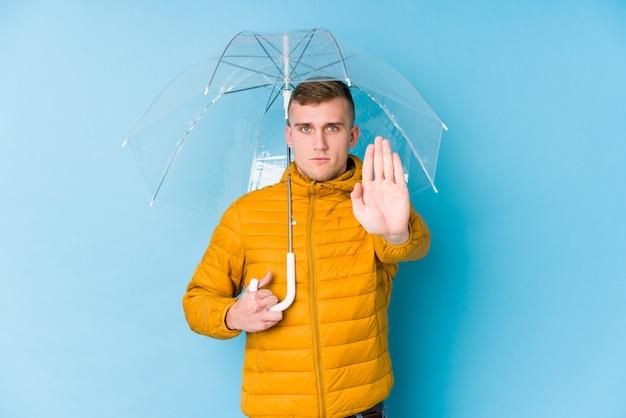 정지 신호를 보여주는 뻗은 손으로 우산 서 들고 젊은 백인 남자, 당신을 방지.