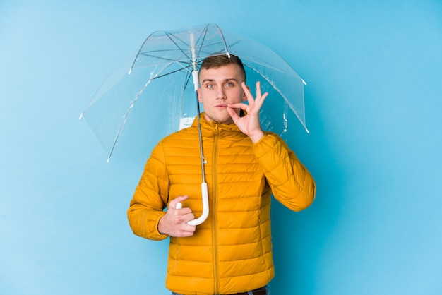 Молодой кавказский человек держа зонтик с пальцами на губах держа в секрете.