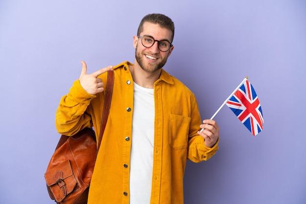 親指を立てるジェスチャーを与える紫色に分離されたイギリスの旗を保持している若い白人男性